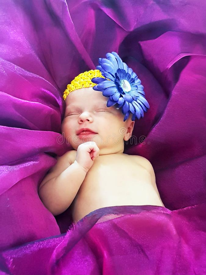 Nyfött behandla som ett barn flickan som ler att sova på sängultravioletlilor royaltyfri fotografi