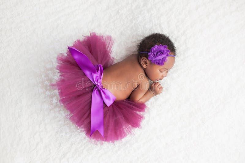 Nyfött behandla som ett barn flickan som bär en purpurfärgad ballerinakjol arkivfoto