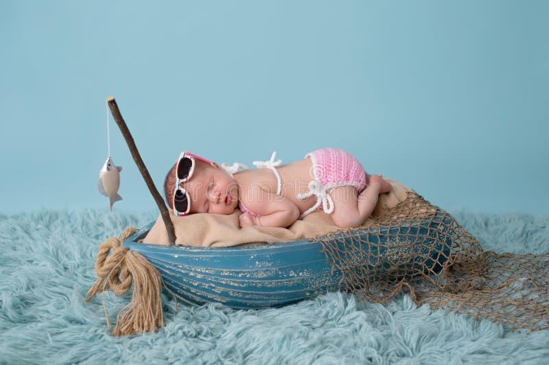 Nyfött behandla som ett barn flickan som sover i en fiskebåt arkivbild