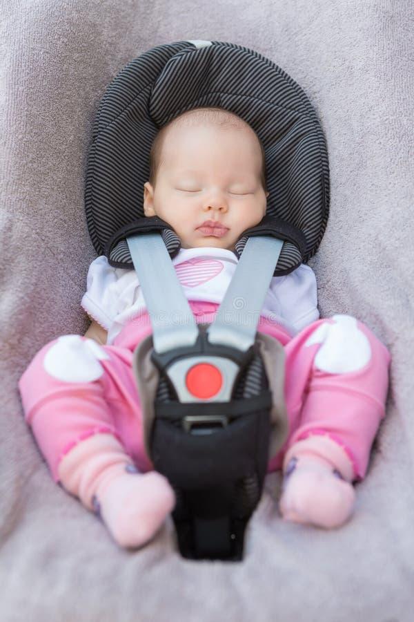 Nyfött behandla som ett barn flickasammanträde i ett bilsäte fotografering för bildbyråer