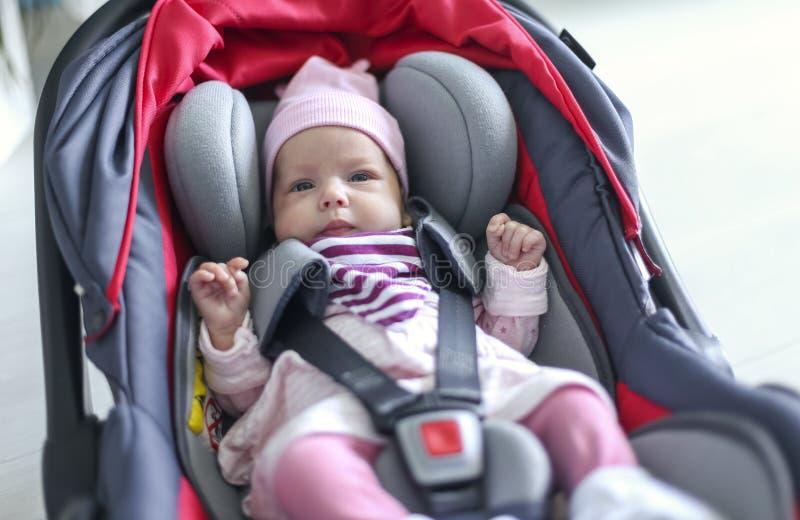 Nyfött behandla som ett barn flickasammanträde i ett bilsäte arkivbilder