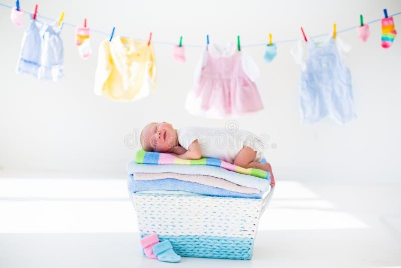 Nyfött behandla som ett barn i en korg med handdukar fotografering för bildbyråer