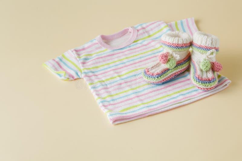 Nyfött behandla som ett barn kläder och skor på beige bakgrund arkivbilder