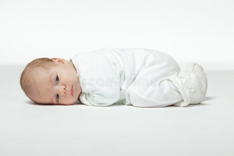 Nyfött behandla som ett barn krullat ligga upp arkivbild