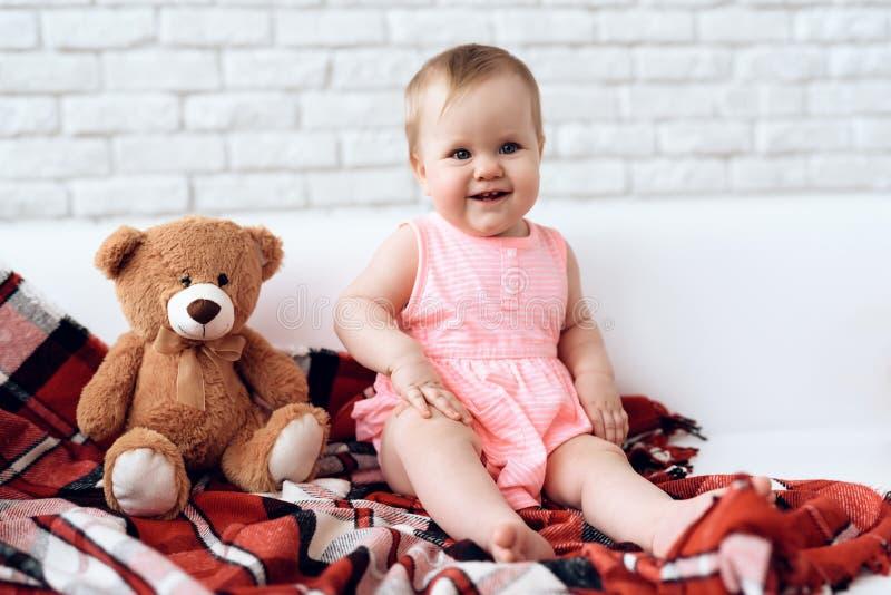 Nyfött behandla som ett barn på soffan med den flotta björnen royaltyfri foto