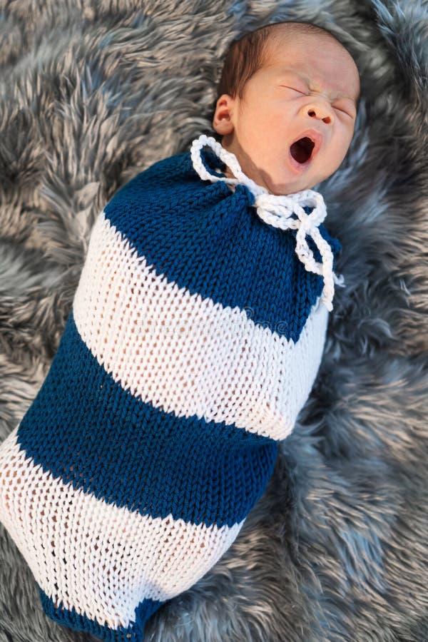 Nyfött behandla som ett barn pojken som gäspar och lindas i en rät maskasjal på säng arkivfoton