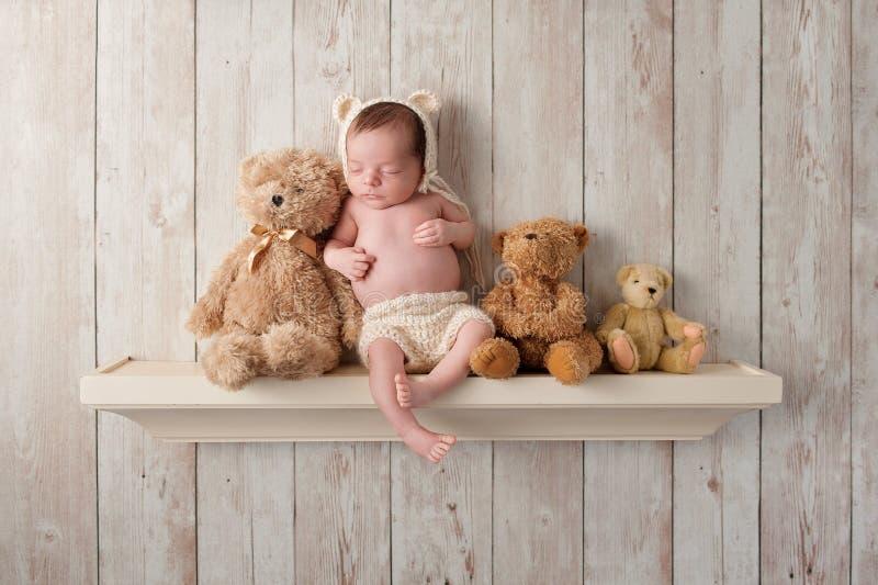 Nyfött behandla som ett barn pojken på en hylla med Teddy Bears arkivfoto