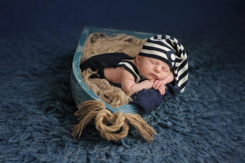 Nyfött behandla som ett barn pojken som sover i ett fartyg arkivbild