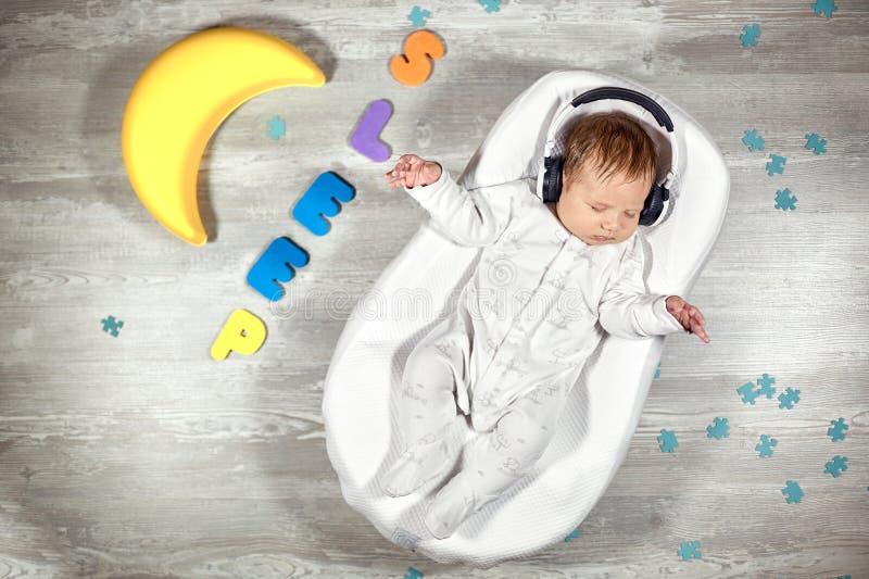 Nyfött behandla som ett barn sömnar i en special ortopedisk madrass för att behandla som ett barn kokong, på mångfärgade bokstäve arkivbild