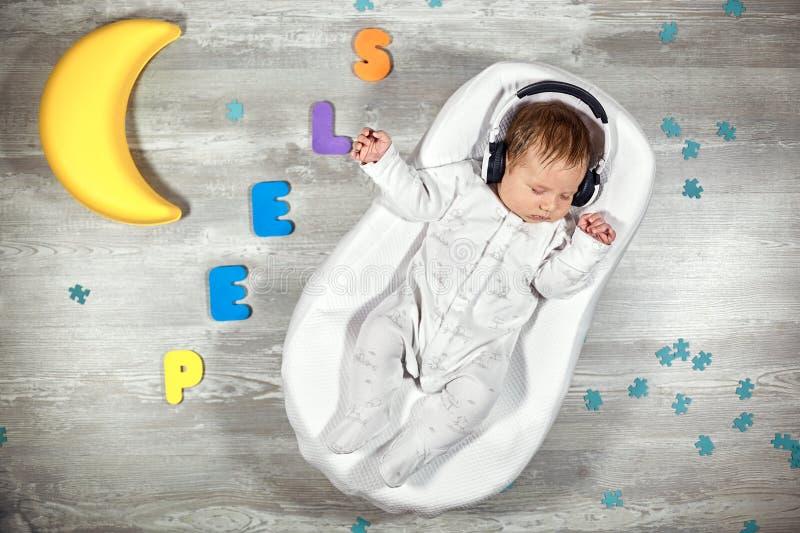 Nyfött behandla som ett barn sömnar i en special ortopedisk madrass för att behandla som ett barn kokong, på mångfärgade bokstäve arkivfoton