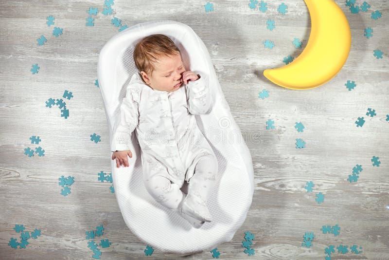 Nyfött behandla som ett barn sömnar i en special ortopedisk madrass för att behandla som ett barn kokong, på ett trägolv, leksakm arkivbild