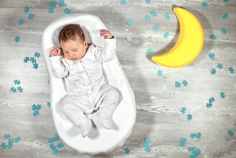Nyfött behandla som ett barn sömnar i en special ortopedisk madrass för att behandla som ett barn kokong, på ett trägolv, leksakm arkivbilder