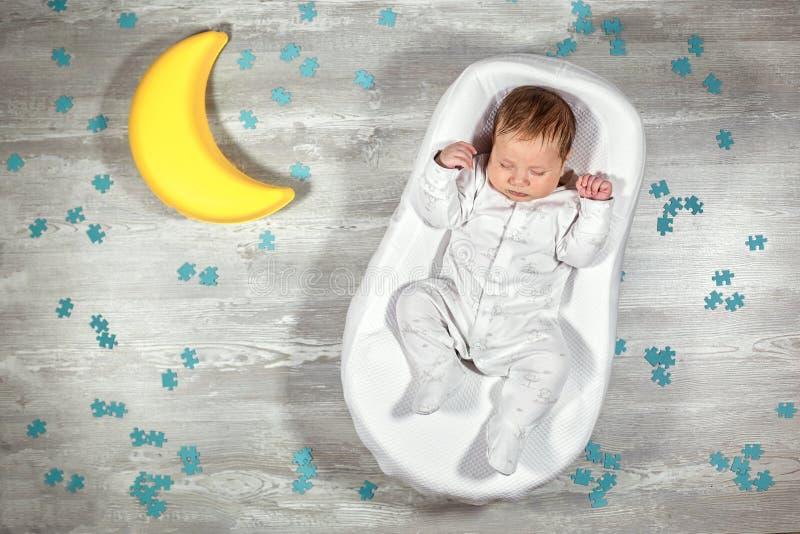 Nyfött behandla som ett barn sömnar i en special ortopedisk madrass för att behandla som ett barn kokong, på ett trägolv, leksakm royaltyfria foton
