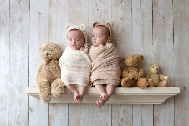 Nyfött behandla som ett barn tvilling- flickor som bär björnhättor arkivbilder