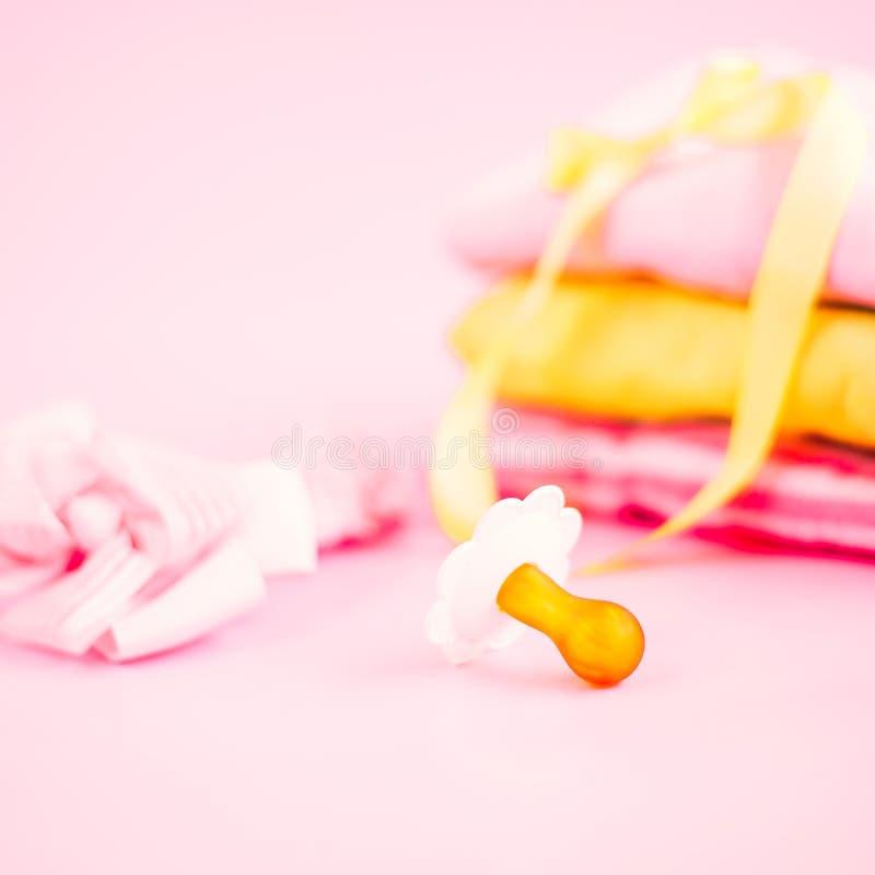 nyfött material, kläder och fredsmäklaren för behandla som ett barn flickan på rosa bakgrund royaltyfri bild