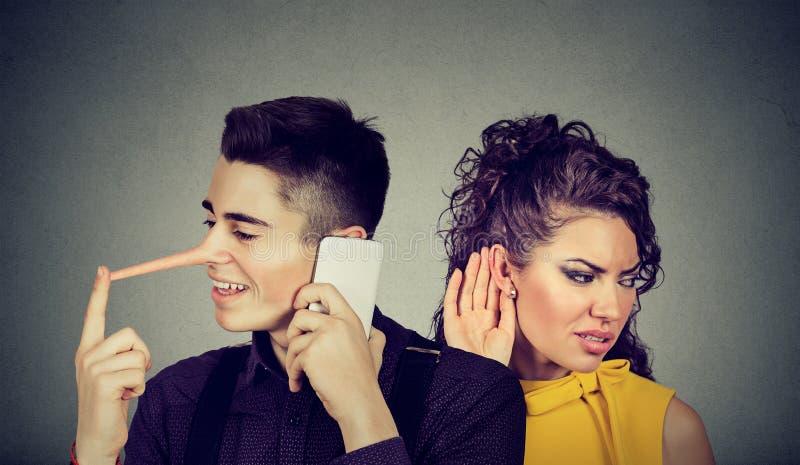 Nyfiken bekymrad kvinna som lyssnar i hemlighet till en lycklig manlögnare som talar på mobiltelefonen med hans vän royaltyfri bild