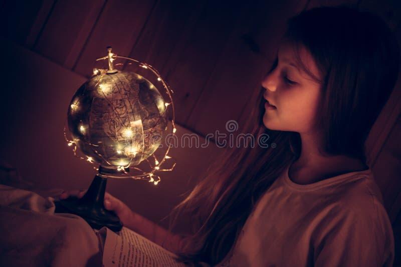 Nyfiken beundra barnflicka med boken i säng som ser glänsande developmen för utbildning för kunskap för kuriositet för begrepp fö fotografering för bildbyråer