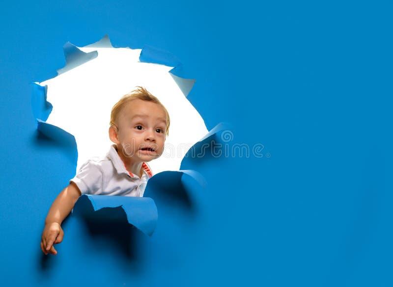 nyfiken cutie Titt f?r litet barn till och med s?nderrivet papper Nyfiken pojkebarnblick ut ur h?let i papper Klipp för liten ung fotografering för bildbyråer