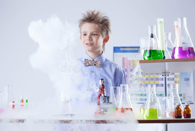 Nyfiken elev som poserar med provrör och flaskor royaltyfria foton