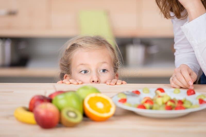 Nyfiken flicka som ser fruktsallad i kök royaltyfria foton