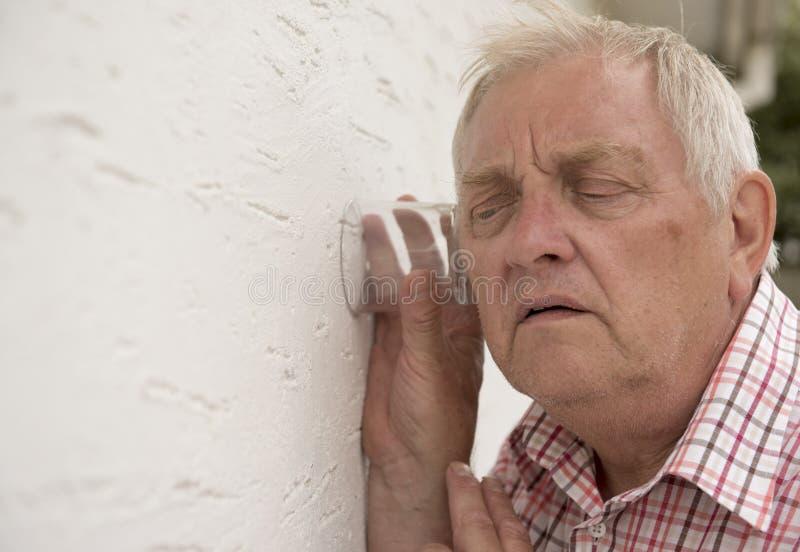Nyfiken granne som upp till rymmer ett exponeringsglas väggen royaltyfria foton