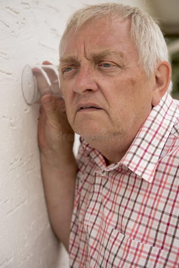 Nyfiken granne som upp till rymmer ett exponeringsglas väggen arkivfoto