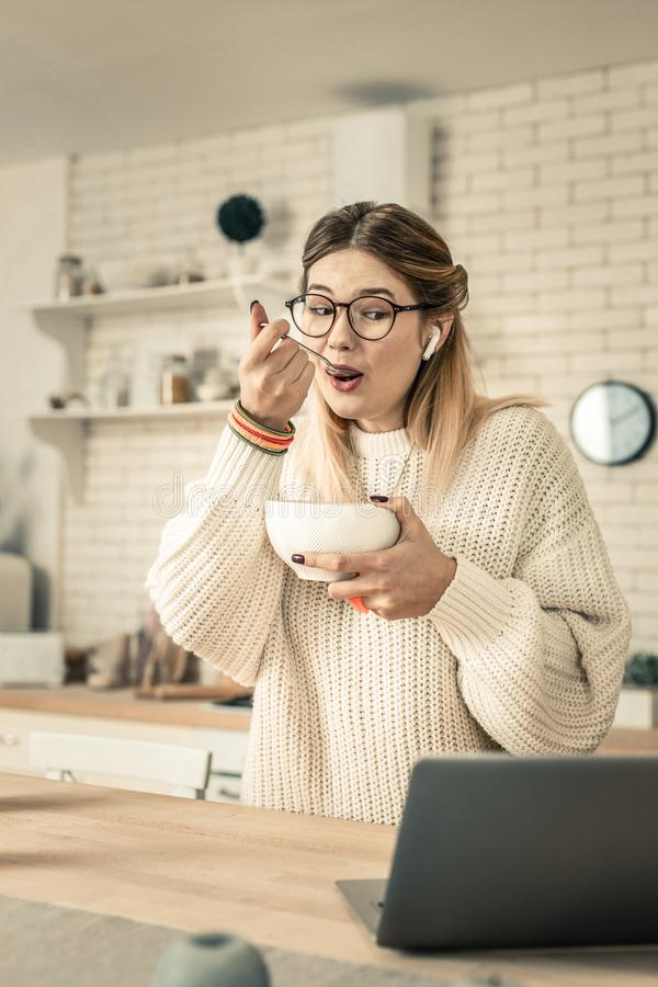 Nyfiken kvinna i den vita tröjan som kastar en blick på bärbar datorskärmen arkivbild