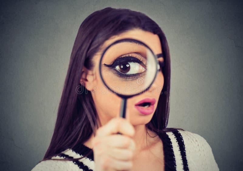 Nyfiken kvinna som ser till och med ett förstoringsglas arkivfoto