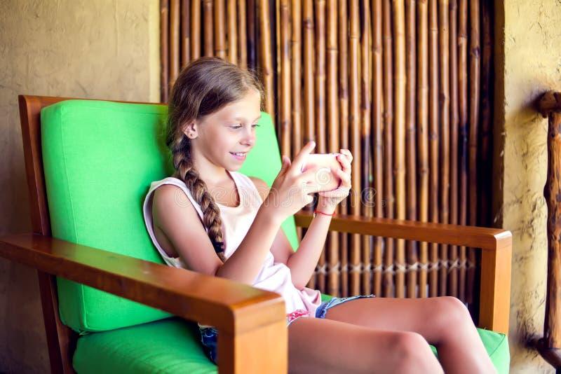 Nyfiken liten flicka som spelar lekar på hennes mobiltelefon inomhus arkivfoto