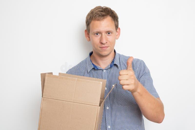 nyfiken man som ser inom en kartong som han rymmer i hans händer på en vit bakgrund fotografering för bildbyråer