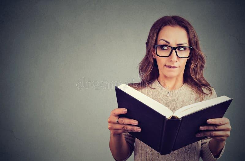 Nyfiken nerdkvinnaläsebok fotografering för bildbyråer