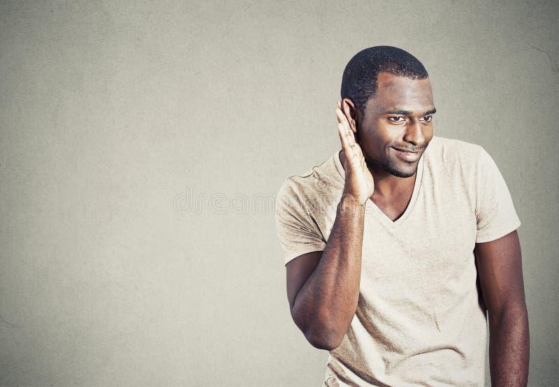 Nyfiken tjuvlyssnande för ung man som lyssnar in på konversation royaltyfri bild
