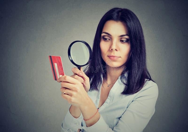 Nyfiken ung affärskvinna som ser kreditkorten till och med förstoringsglaset royaltyfria foton