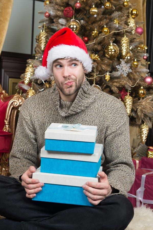 Nyfiket vad är inom Gåvor för manhållxmas Santa Claus med xmas-gåvor Man i den röda santa hatten Glad jul och arkivfoton