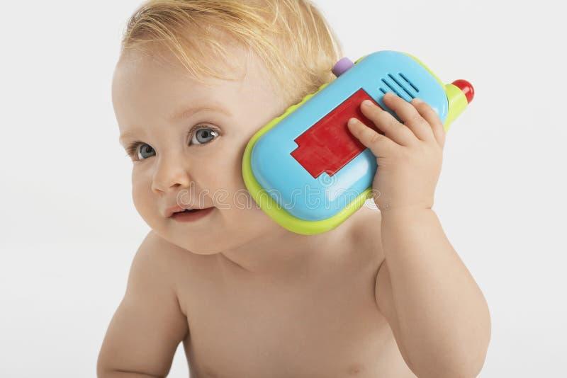 Nyfikna Little Boy genom att använda Toy Phone arkivbild