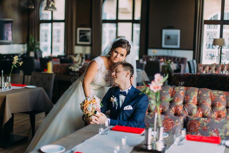 Nygift person enloved par Charmig brud i den vita klänningen som står nära stilig stylishgroom som inomhus poserar, ljus lyx royaltyfri foto