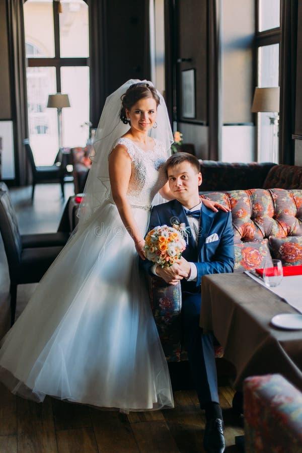Nygift person enloved par Härlig brud i den vita klänningen som står nära det stiliga brudgumblåttföljet som inomhus poserar, lyx arkivbild