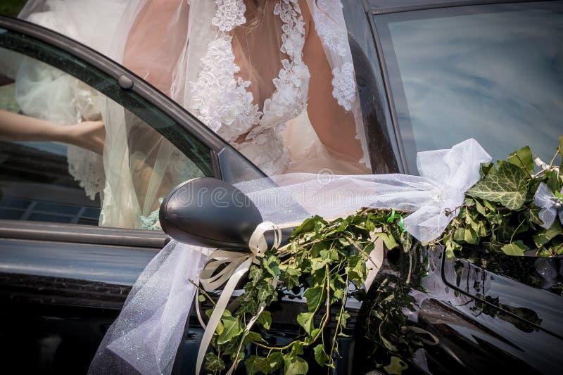 Nygift personbrud i dekorerad gifta sig bil royaltyfri fotografi