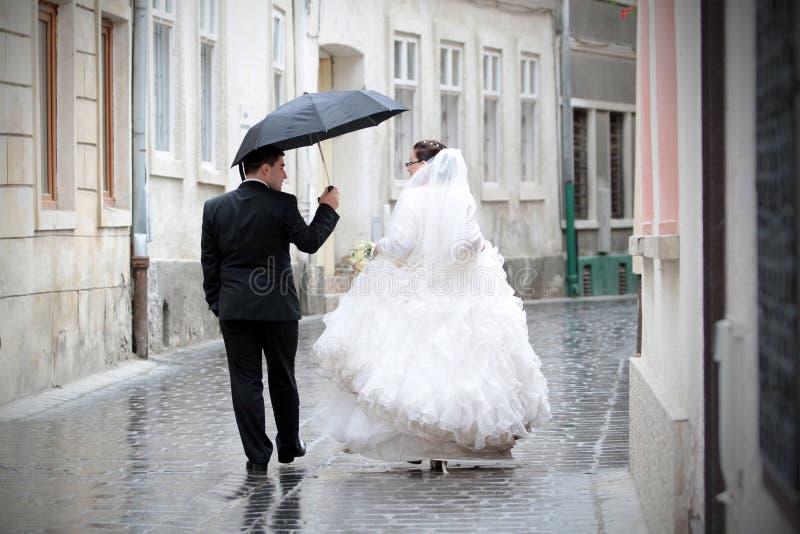 Nygift personpar i regn royaltyfri foto