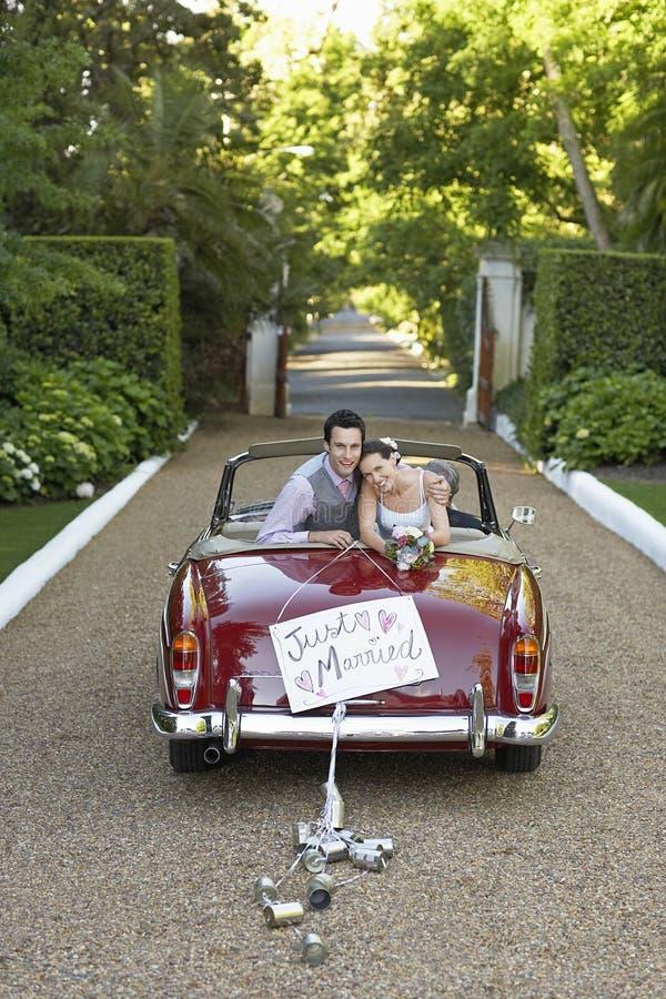 Nygift personpar i Retro bröllopbil arkivbilder