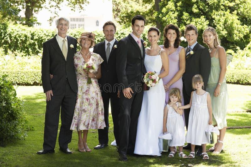 Nygift personpar med bröllopgäster i trädgård royaltyfria bilder