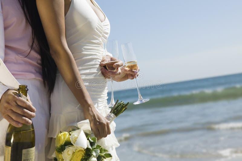 Nygift personpar med den Champagne Bottle And Flutes On stranden royaltyfria foton