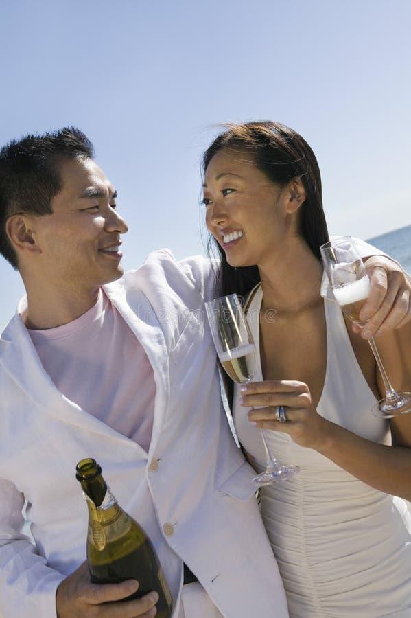Nygift personpar med den Champagne Bottle And Flutes On stranden arkivfoto