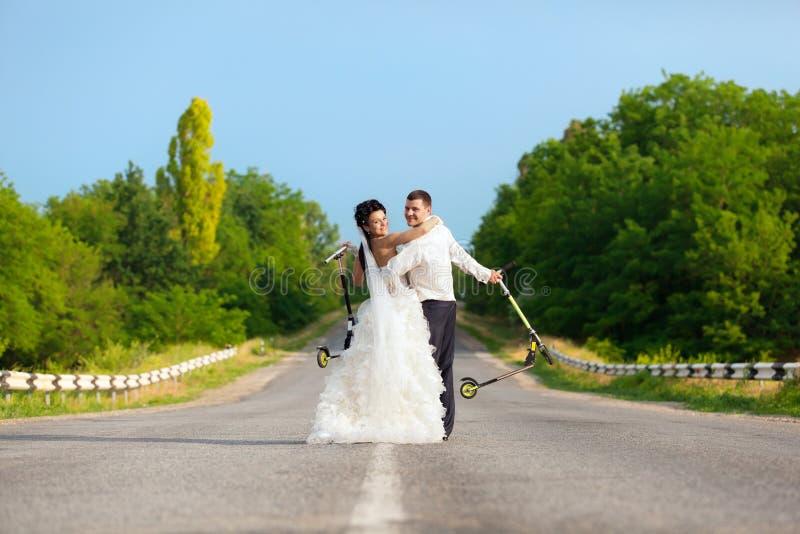 Nygift personpar med sparkcyklar arkivbild