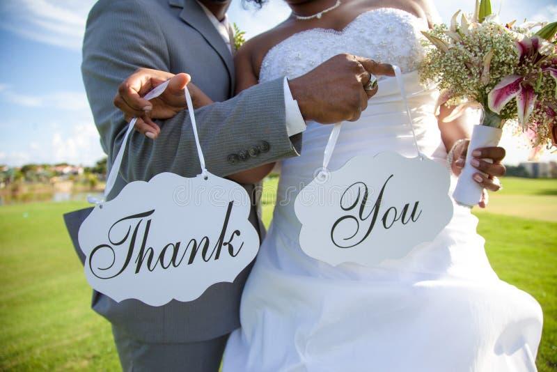 Nygift personpar med tackar dig att underteckna royaltyfri fotografi