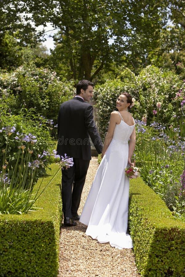 Nygift personpar som går i trädgård arkivbilder