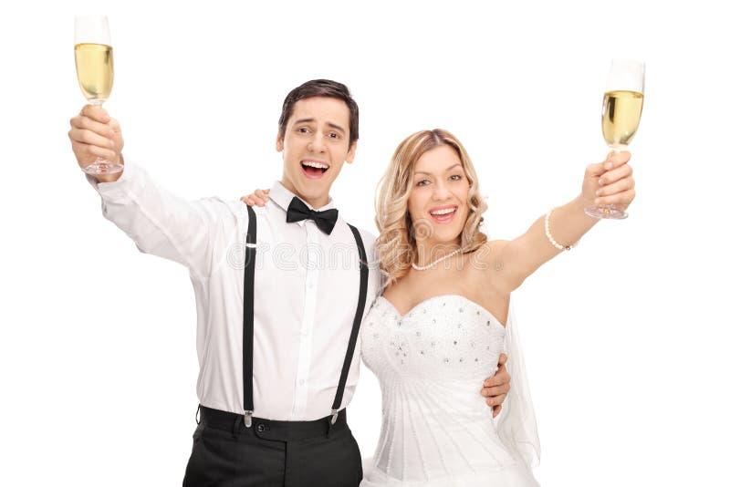 Nygift personpar som gör ett rostat bröd med vin fotografering för bildbyråer