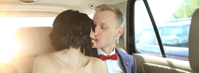 Nygift personpar som kysser i bröllopbillimousine royaltyfri fotografi