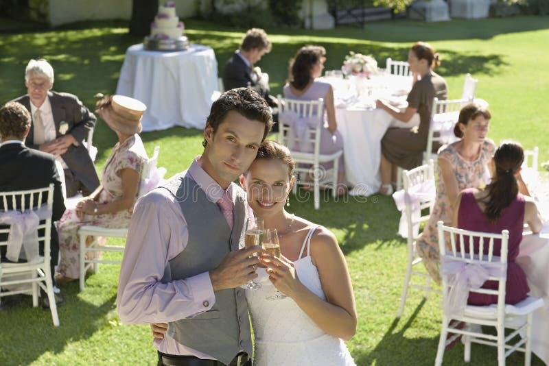 Nygift personpar som rostar Champagne In Garden royaltyfri foto