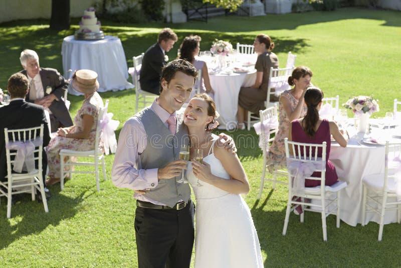 Nygift personpar som rostar Champagne In Garden arkivbilder